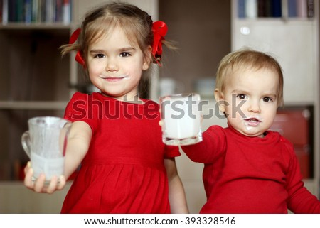 Happy little children with milk mustache â?? brother and sister â?? showing an empty glass of milk at home, food and drink concept, healthy food, indoor - stock photo