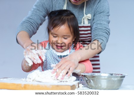 Happy Little Chinese Girl Knead Dough with her Mother indoor