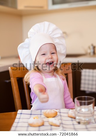 Happy little cook girl sitting at kitchen table with cookies and glass of water