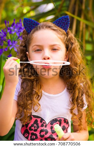 Happy little curly girl playing with soap bubbles on a summer nature, wearing a blue ears of tiger accessories over her head in a blurred nature background