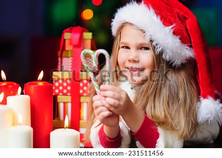 happy little fashion girl in Santa Hat with Christmas light and eve and candy - stock photo
