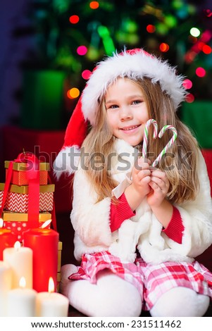 happy little fashion girl in Santa Hat with Christmas light and eve and candy
