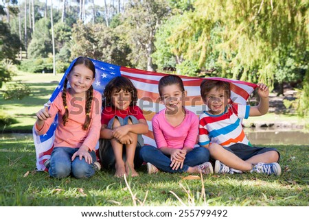 Happy little friends with american flag on a sunny day - stock photo