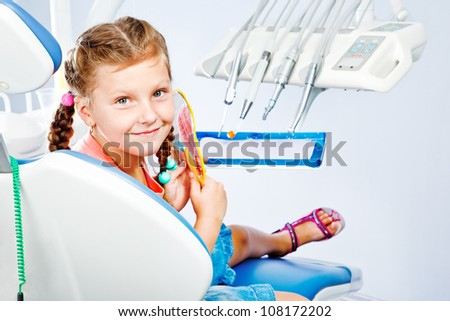 Happy little girl after dental treatment - stock photo