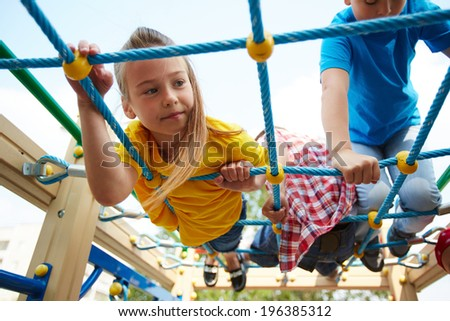 Happy little girl and her friends on playground area