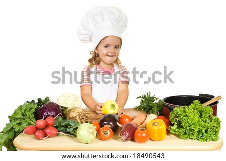 Happy little girl as a chef preparing vegetables for cooking - isolated - stock photo