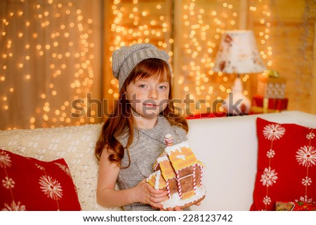happy little girl at home holding a gingerbread house. christmas,illuminations - stock photo