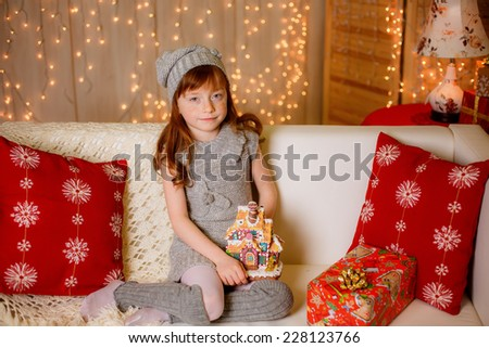 happy little girl at home holding a gingerbread house. christmas, New Year`s decorations, illuminations - stock photo