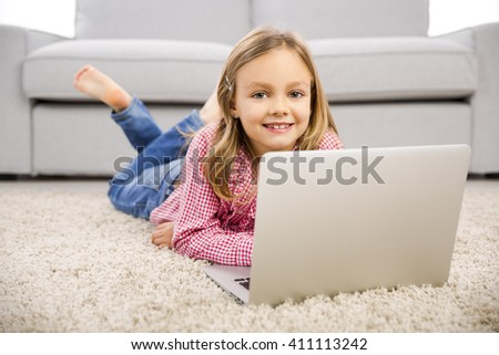 Happy little girl at home working with a laptop - stock photo
