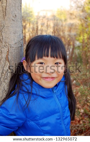 Happy little girl at outdoor during autumn