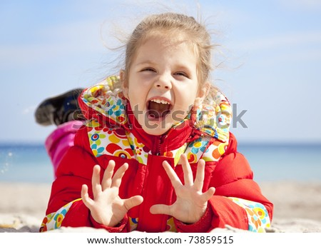 Happy little girl at the beach in spring time. - stock photo