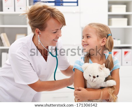 Happy little girl at the doctor for a checkup - being examined with a stethoscope - stock photo