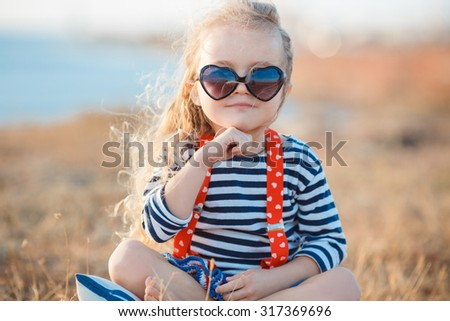 happy little girl at the seaside in the summer.Adorable little girl at beach during summer vacation. Happy baby with sunglasses by the sea - stock photo
