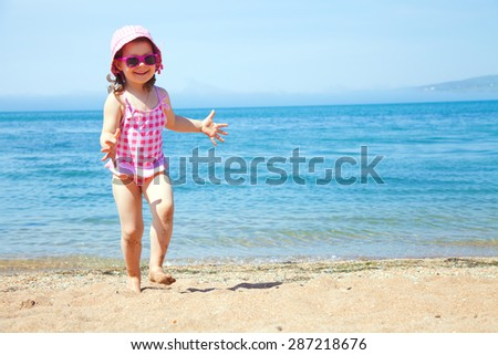 happy little girl at the seaside in the summer time - stock photo