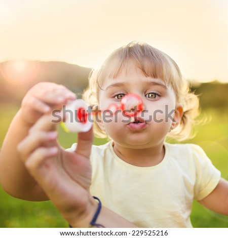 Happy little girl blowing bubbles in summer nature - stock photo
