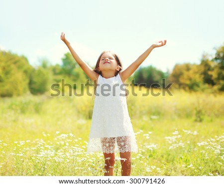 Happy little girl child enjoying sunny summer day and having fun outdoors - stock photo