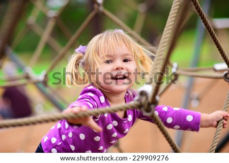 Happy little girl climbing on outdoor playground - stock photo