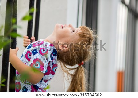 Happy little girl climbing on outdoor playground