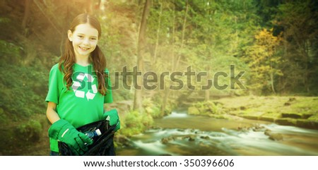 Happy little girl collecting rubbish against rapids flowing along lush forest - stock photo