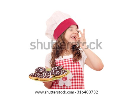 happy little girl cook with chocolate donuts and ok hand sign - stock photo