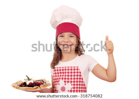 happy little girl cook with crepes and thumb up - stock photo