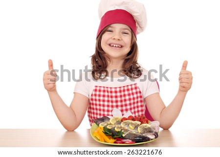 happy little girl cook with fish and thumbs up - stock photo