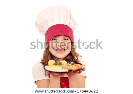 happy little girl cook with salmon fish portion - stock photo
