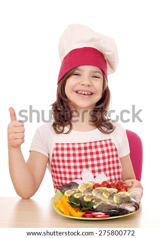 happy little girl cook with trout and thumb up - stock photo