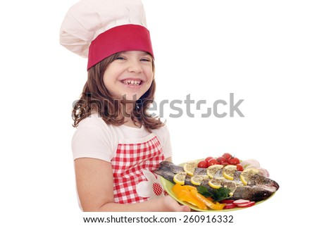 happy little girl cook with trout on plate - stock photo