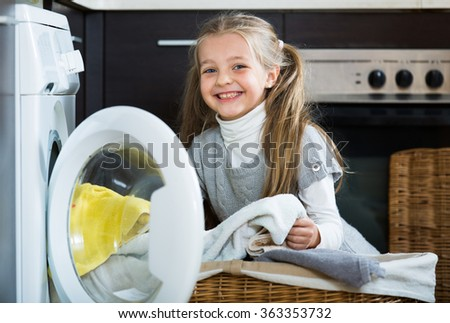 Happy little girl doing laundry in home interior
