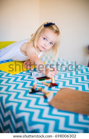 Happy little girl drawing art at dining table