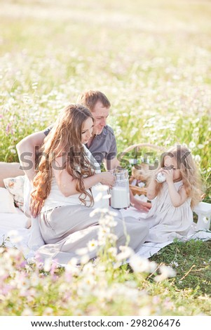 happy little girl drinking milk in the camomile field. picnic - stock photo