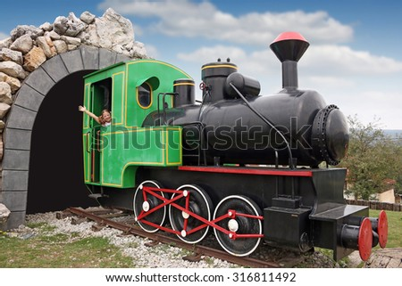 happy little girl driving a old steam locomotive - stock photo