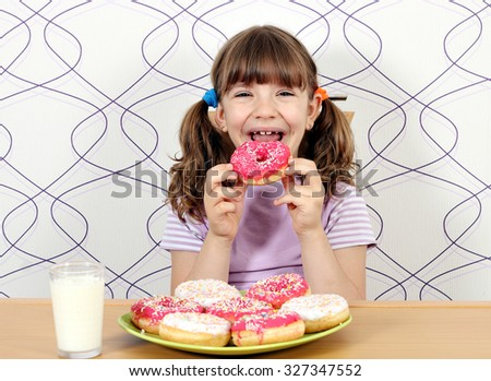 happy little girl eating donuts - stock photo