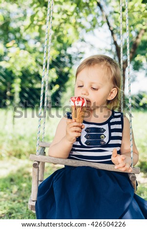 Happy little girl eating ice cream on the swing - stock photo