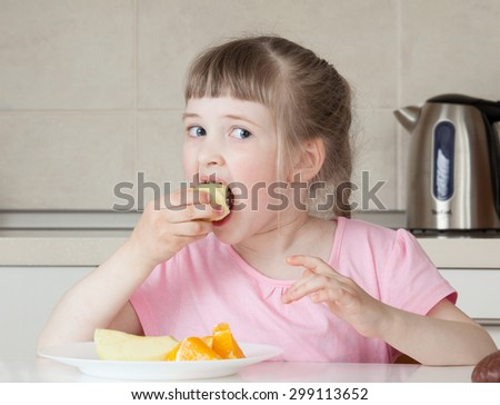 Happy little girl eating tasty food at home - stock photo