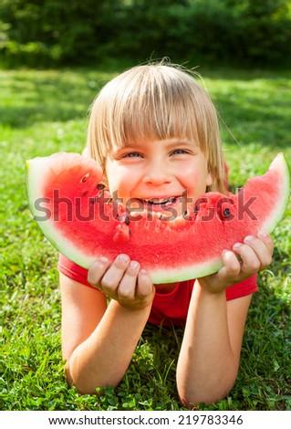 Happy little girl eating watermelon in a garden - stock photo