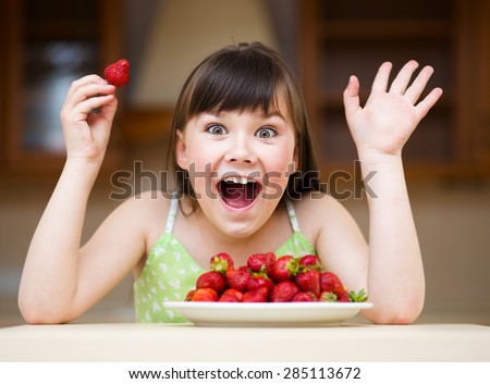 Happy little girl eats strawberries - stock photo