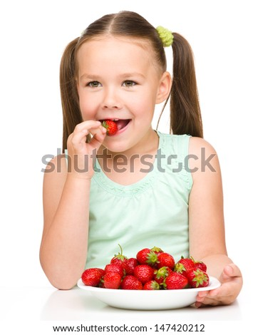 Happy little girl eats strawberries and shows the thumb up sign, isolated over white - stock photo