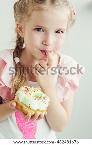 happy little girl eats the sweet donut on a white background