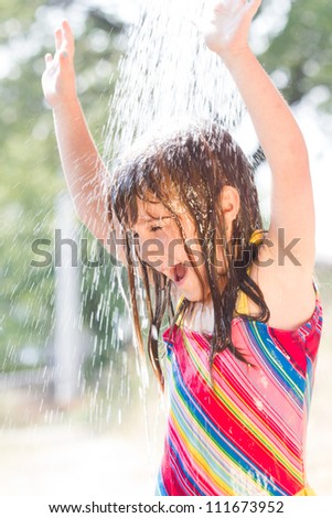 Happy little  girl enjoying in summer day and playing with water - stock photo