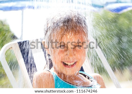 Happy little  girl enjoying in summer day and playing with water