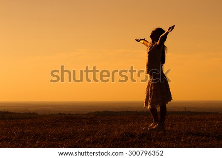 Happy little girl enjoys in sunset.Greeting the sunset - stock photo