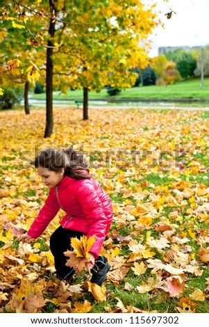 happy little girl have fun playing with fallen golden leaves - stock photo