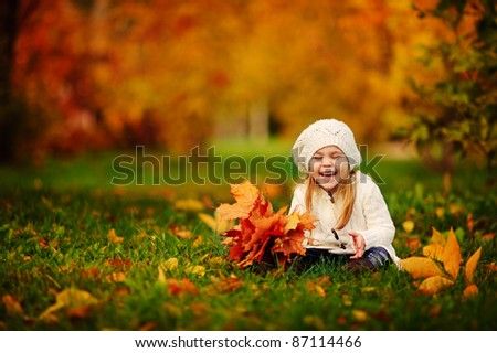 happy little girl have fun playing with fallen golden leaves