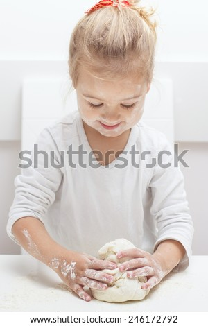 Happy little girl have fun with kneading dough at home.