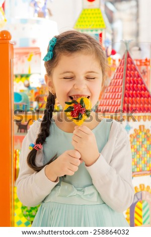 Happy little girl having fun and licking candy - stock photo
