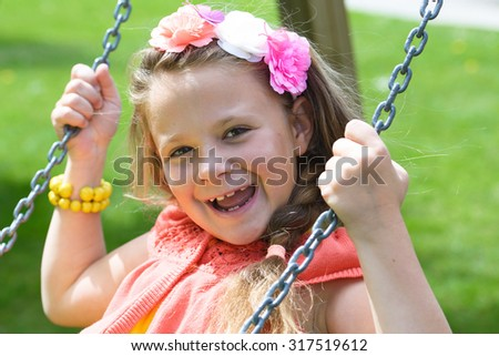 Happy little girl having fun on a swing outdoor