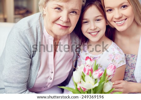 Happy little girl, her mother and grandmother with fresh tulips - stock photo