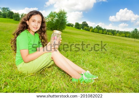 Happy little girl hold jar with butterfly, sitting in the field in the park on sunny summer day